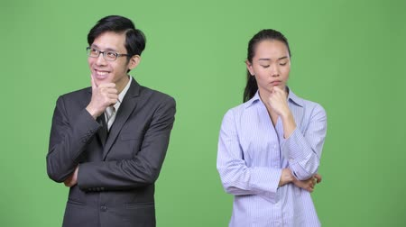 hand on chin : Young Asian business couple thinking together Stock Footage