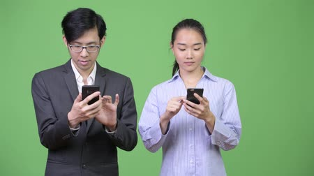 together trust : Young Asian business couple using phone together