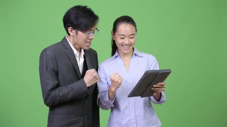 raising fist : Young Asian business couple getting good news together Stock Footage