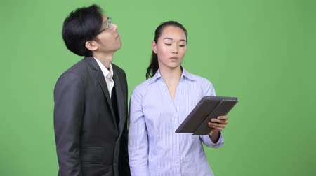 polegar : Young Asian business couple getting bad news together
