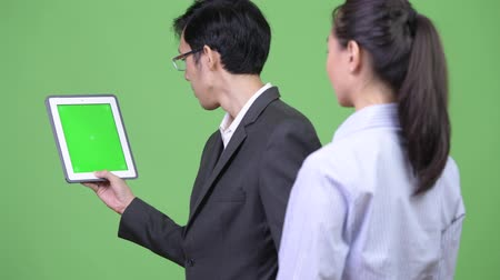 together trust : Young Asian business couple using digital tablet together