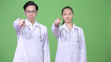 together trust : Young Asian couple doctors pointing at camera together