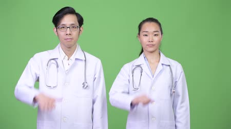 together trust : Young Asian couple doctors giving thumbs down together Stock Footage