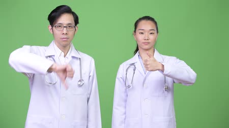 confuso : Young Asian couple doctors having different decisions together
