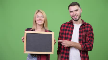 клетчатый : Young couple holding blackboard and pointing finger together