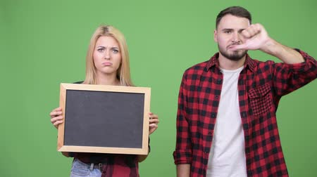 tablica : Young couple holding blackboard giving thumbs down together