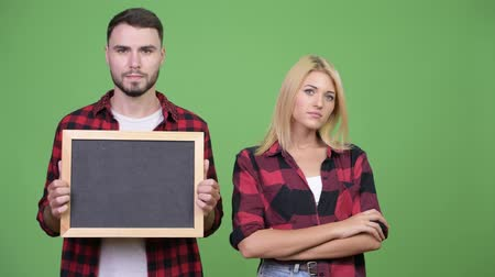 crossed : Young couple holding blackboard and arms crossed together