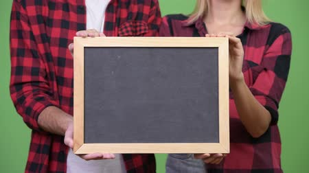 клетчатый : Young couple holding blackboard together Стоковые видеозаписи