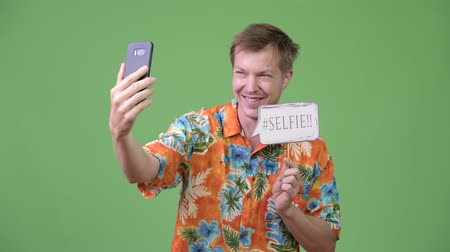 гавайский : Young handsome tourist man taking selfie with paper sign