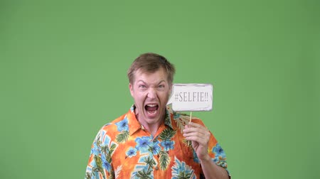 гавайский : Young handsome tourist man screaming with selfie paper sign