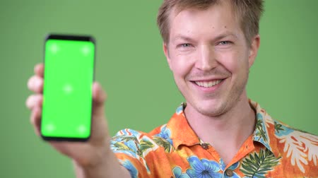 гавайский : Young happy handsome tourist man smiling while showing phone