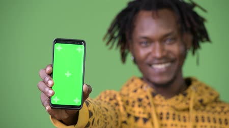 hippi : Young happy handsome African man smiling while showing phone Stok Video