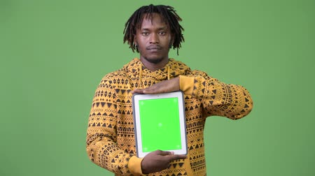 hippi : Young handsome African man showing digital tablet Stok Video