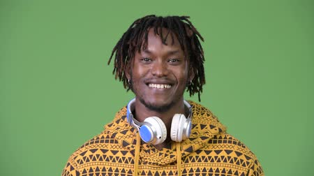 hippi : Young happy handsome African man smiling while wearing headphones Stok Video