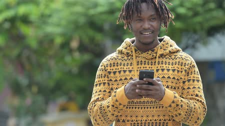 hippi : Young handsome African man using phone in the streets outdoors