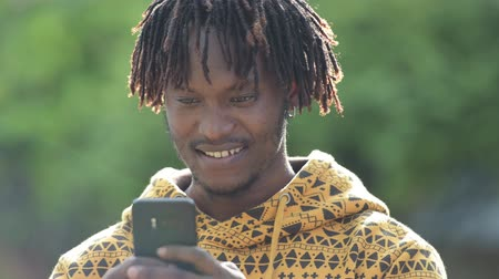 hippi : Young happy handsome African man smiling while using phone in the streets outdoors