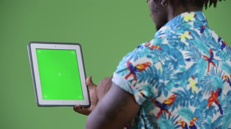 hippi : Young handsome African tourist man using digital tablet Stok Video