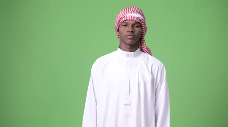 the bedouin : Young African man wearing traditional Muslim clothes against green background Stock Footage