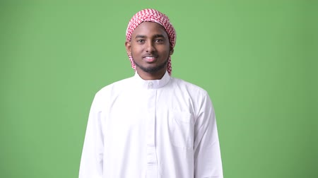 the bedouin : Young handsome African man wearing traditional Muslim clothes against green background Stock Footage
