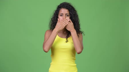 covering : Young beautiful Hispanic woman covering mouth as three wise monkeys concept
