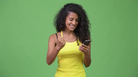 kolsuz : Young beautiful Hispanic woman using phone and getting good news