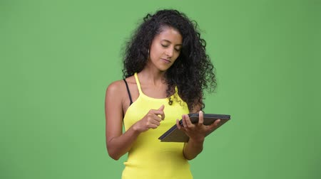 kolsuz : Young beautiful Hispanic woman thinking while using digital tablet