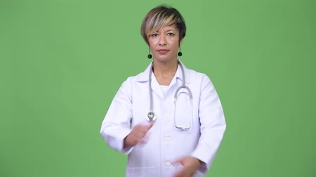 crossed arms : Happy mature beautiful multi-ethnic woman doctor