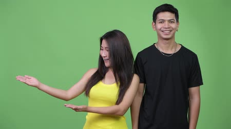 together trust : Young Asian couple showing something together Stock Footage