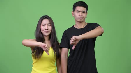 together trust : Young angry Asian couple giving thumbs down together Stock Footage