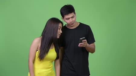 aparat ortodontyczny : Young happy Asian couple using phone together Wideo