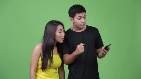 raising fist : Young Asian couple using phone and getting good news together