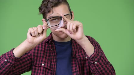 nagyító : Young handsome teenage nerd boy playing with magnifying glass
