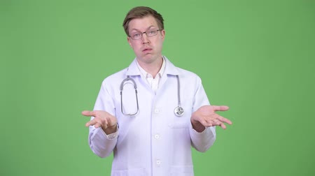 disinterest : Portrait Of Young Man Doctor Shrugging Shoulders