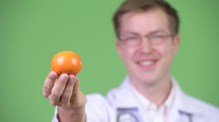personal medico : Retrato del hombre joven Doctor Holding Orange Fruit Archivo de Video