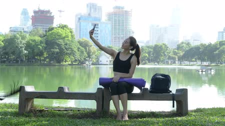 vlogging : Woman Sitting In Park And Using Mobile Phone Stock Footage