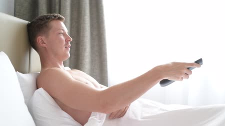watch tv : Man In Bed Watching Television And Holding Tv Remote