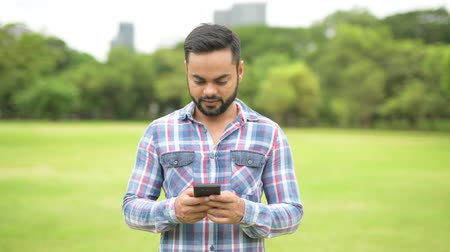 paquistão : Young Handsome Indian Man In Park Using Mobile Phone