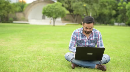paquistão : Young Handsome Indian Man In Park Using Laptop Computer