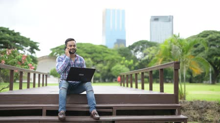 indian ethnicity : Young Handsome Indian Man In Park Using Laptop Computer