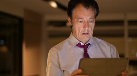 ciddi : Mature Businessman In Office At Night Using Digital Tablet Computer