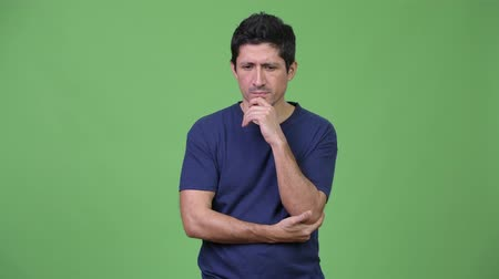 hand on chin : Serious Hispanic man thinking against green background