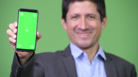 perui : Happy Hispanic businessman showing phone