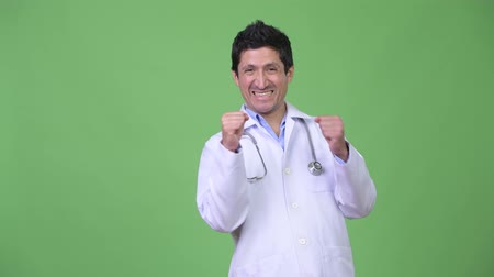 raising fist : Happy Hispanic man doctor looking excited Stock Footage