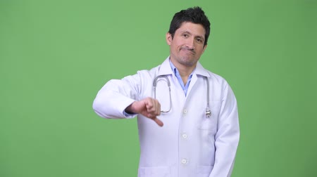 перуанский : Serious Hispanic man doctor giving thumbs down