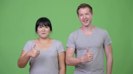 finnish : Young multi-ethnic couple giving thumbs up together