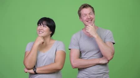 ponderar : Young happy multi-ethnic couple thinking together
