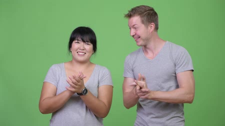 finnish : Young happy multi-ethnic couple clapping hands together Stock Footage