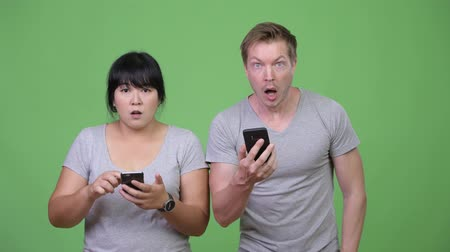 finnish : Young multi-ethnic couple using phone and looking shocked together Stock Footage