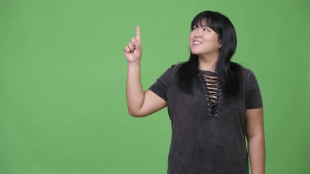 pankáč : Happy overweight Asian woman thinking while pointing finger up