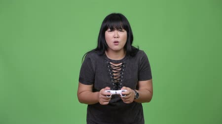 raising fist : Beautiful overweight Asian woman playing games and winning Stock Footage